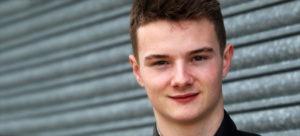 ben hingeley racing driver stood against a roller shutter door smiling