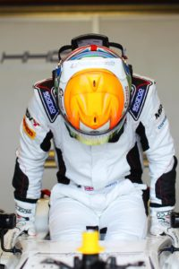 ben getting out of his car, his head is facing down showing the orange detail of his crash helmet