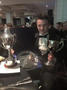 ben at a dinner bash holds up his three trophies