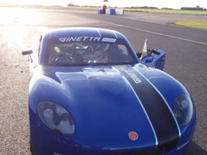 ben sits in a blu car with ginetta emblazoned on the livery