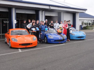 the drivers stand next to all 3 track cars