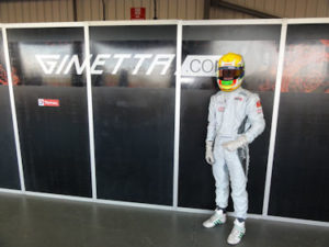 ben in his kit and helmet next to a ginetta sign