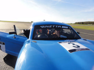 beninthe driving seat of a blue car with the number 3 on thebonnet